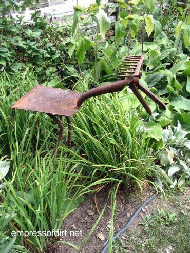 Garden junk tool art creature with a shovel body, rebar legs, rake head and clippers for a beak.