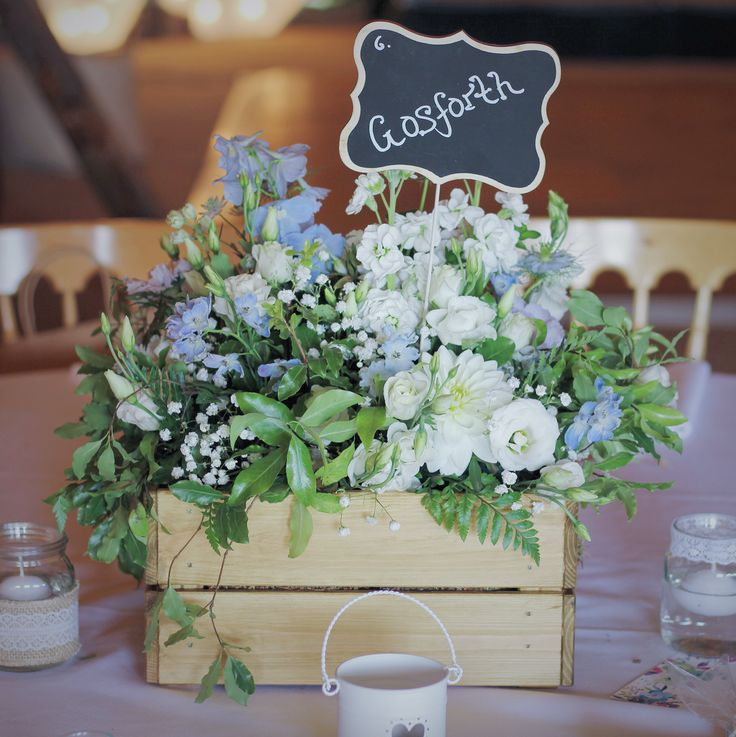 Flowers by Jennifer Pinder. White and blue flowers in a rustic crate for a countryside wedding. Including stock, hydrangea, delphinium, nigella and lisianthus. A lovely pale blue theme for a tipi wedding at Chafford Park in Kent.