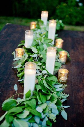 Farm wedding centerpiece with candles and mercury glass votives and greenery runner.