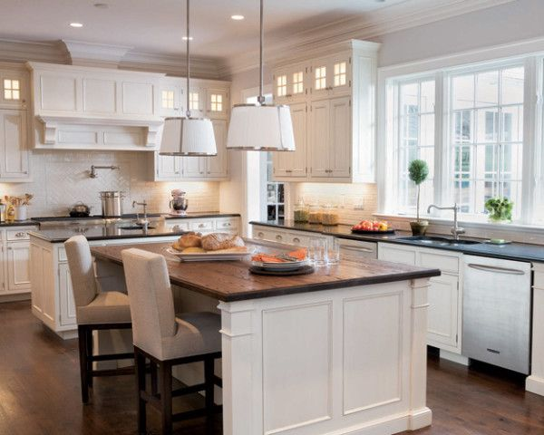 The 17-by-23-foot kitchen's two islands afford easy traffic flow. The smaller one (4 feet square), with a built-in sink and a quartz work surface, is ideal for food prep; the larger one (7 by 4 feet), with a dark-stained oak top, is great as a buffet. Two side-by-side gas ranges enable efficient cooking for large groups.