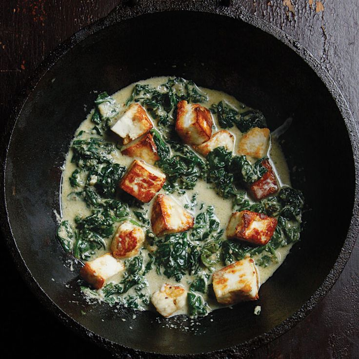 Saag Paneer (Spinach with Fresh Indian Cheese)-- It's not hard to love North Indian saag paneer—meltingly soft spinach strewn with chunks of mild paneer, or fresh cheese—especially when scooped up with hot flatbread.