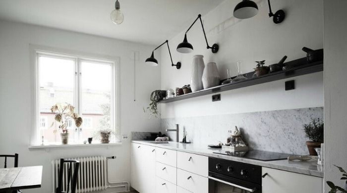A white kitchen incorporating black metal accents with black lamps fixed above the kitchen shelves.