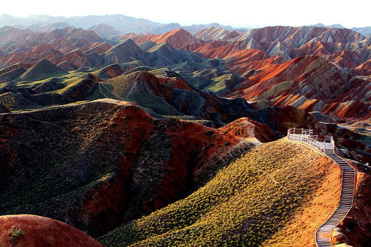 "Zhangye Danxia Landform Geological Park - Gansu Province, China This zebra-like pattern in the mountains was created by different layers of red sandstone and other mineral deposits being compressed together over millions of years. The resulting ""layer cake"" was then cleaved and buckled into its current position by the same tectonic plates responsible for creating parts of the Himalayan mountains."