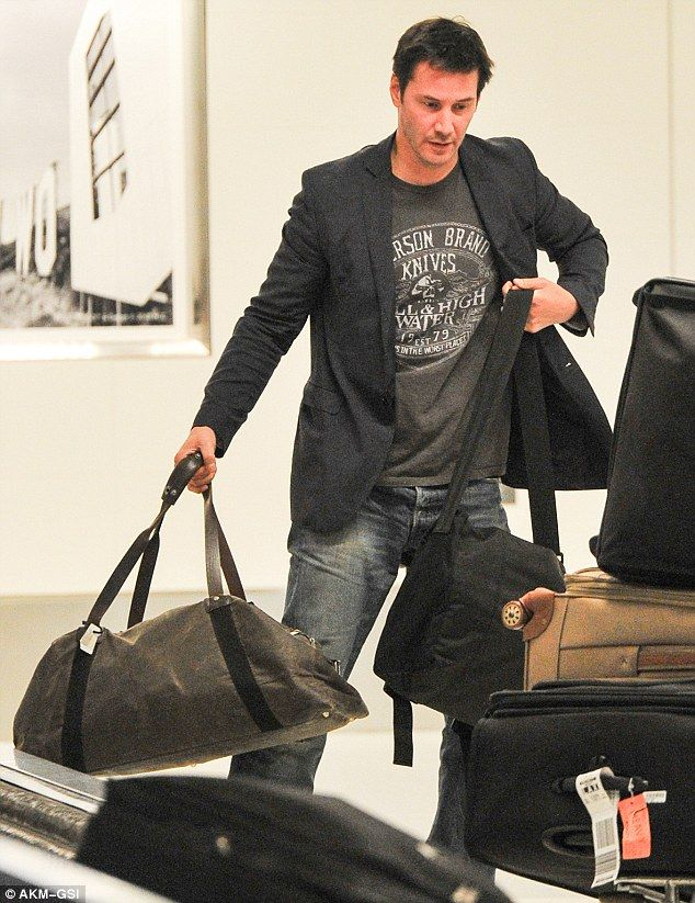 Landing in LA: Clean shaven Keanu dressed for his air travel in distressed denim jeans, a gray Emerson Brand knives t-shirt, a blue blazer, and beige shoes