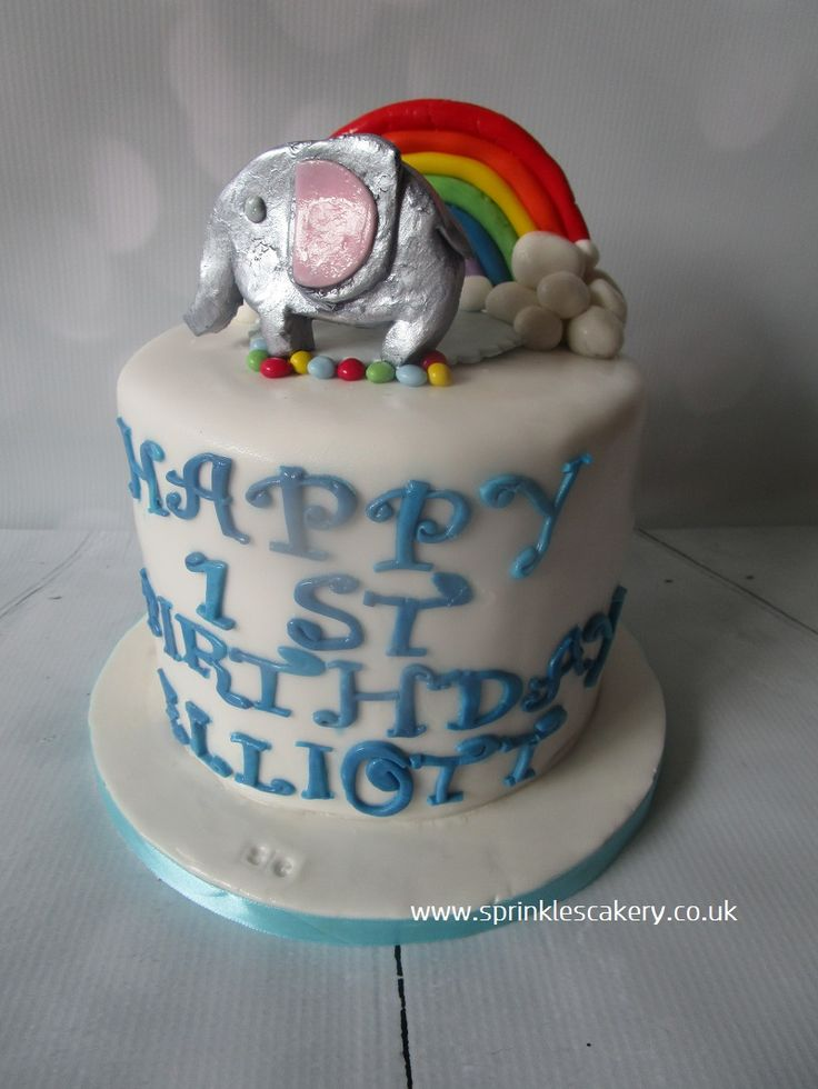 This 1st birthday cake was finished with an edible metallic elephant and rainbow topper.