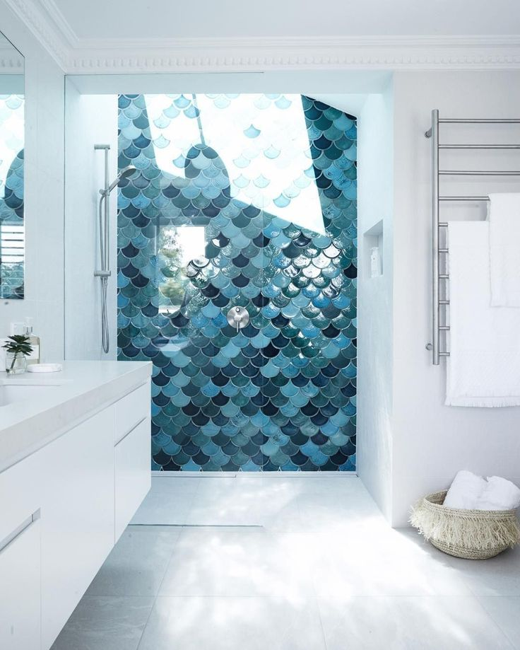 A stunning shower with a skylight and teal scallop tile wall in shower // by Three Birds Renovations
