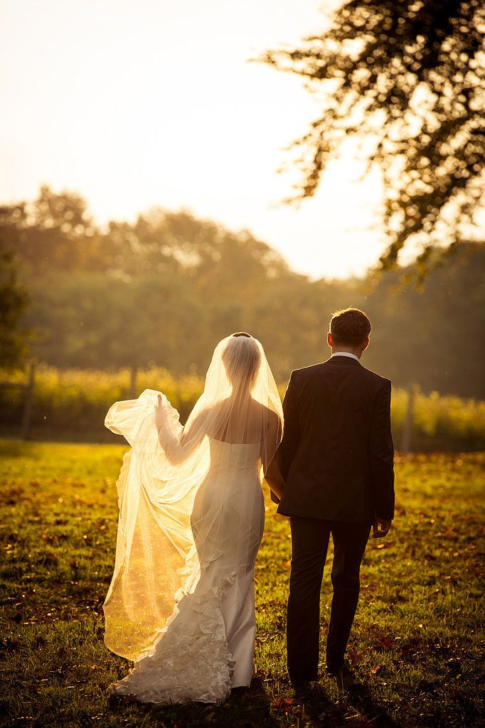 If your ceremony is happening around sunset, use the light to your best advantage. Ask the photographer to scout out an area that'll allow the evening light to illuminate your dress and veil. Photo by Susan Stripling Photographer via Style Me Pretty