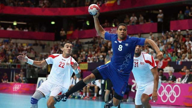 Daniel Narcisse of France shoots and scores between Oussama Boughanmi and Marouan Chouiref of Tunisia in the men's Preliminaries Group A match between France and Tunisia on Day 6.