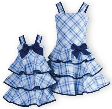 Perfectly matching brother-sister outfits of blue plaid cotton. Girls tiered dresses with navy trim and bows. Fully lined. Button back closures. Mach
