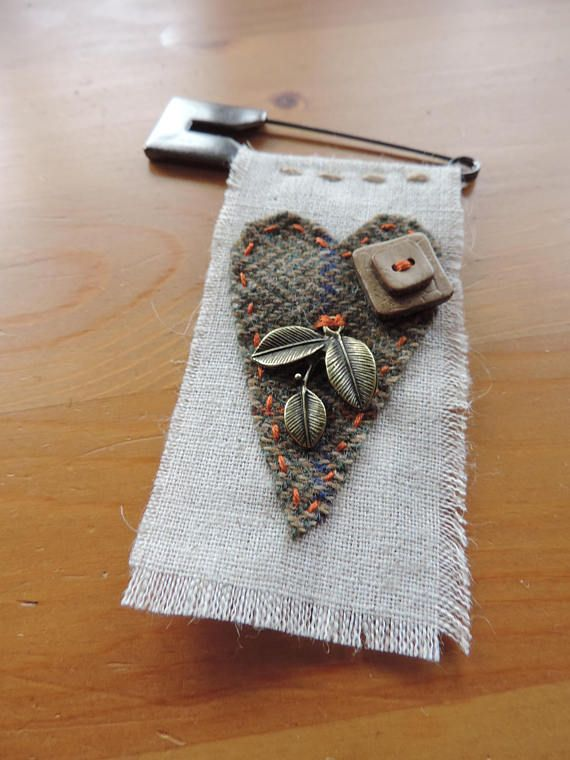 A hand sewn brooch featuring a kilt pin made from linen or tweed with ribbon, charm or button embellishments, which may vary. If there is a particular tweed or ribbon colour and type of embellishment that you prefer, please email me with regards to availability. Size: Kilt pin is
