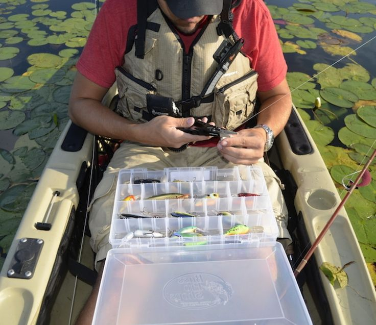 Ben Duchesney attaches a fishing lure to his line while sitting in his fishing kayak.