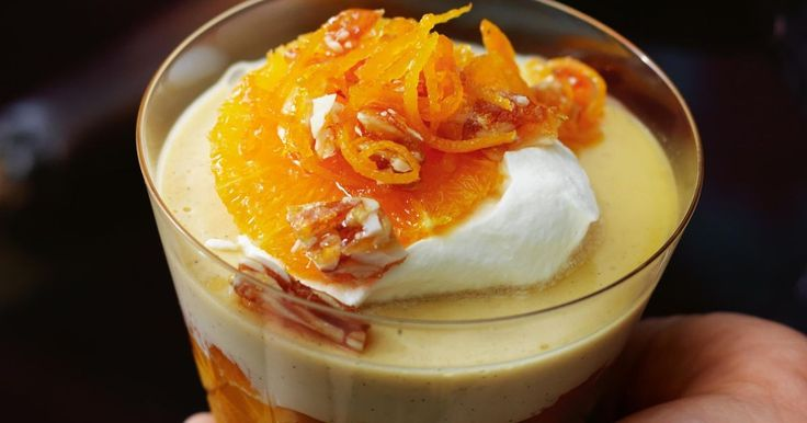 Dip your spoon into this zesty orange trifle toppped with cream, orange slices, syrup, candied zest and almond brittle.