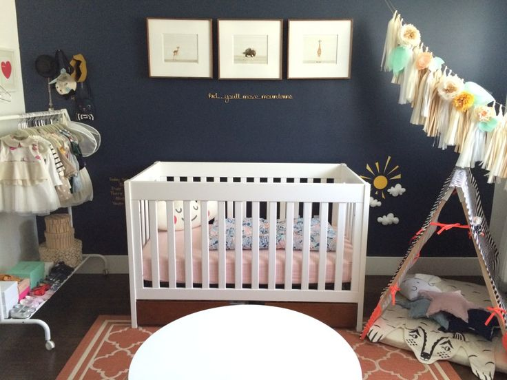 This nursery is right on trend with a navy accent wall! {Plus, I spy adorable wall art from @The Animal Print Shop by Sharon Montrose} #nursery #walldecor