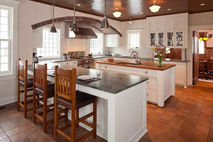 The kitchen has an unusual but practical configuration, offering a room-dividing peninsula, a prep island with a second sink, and a pass-through to the dining room.