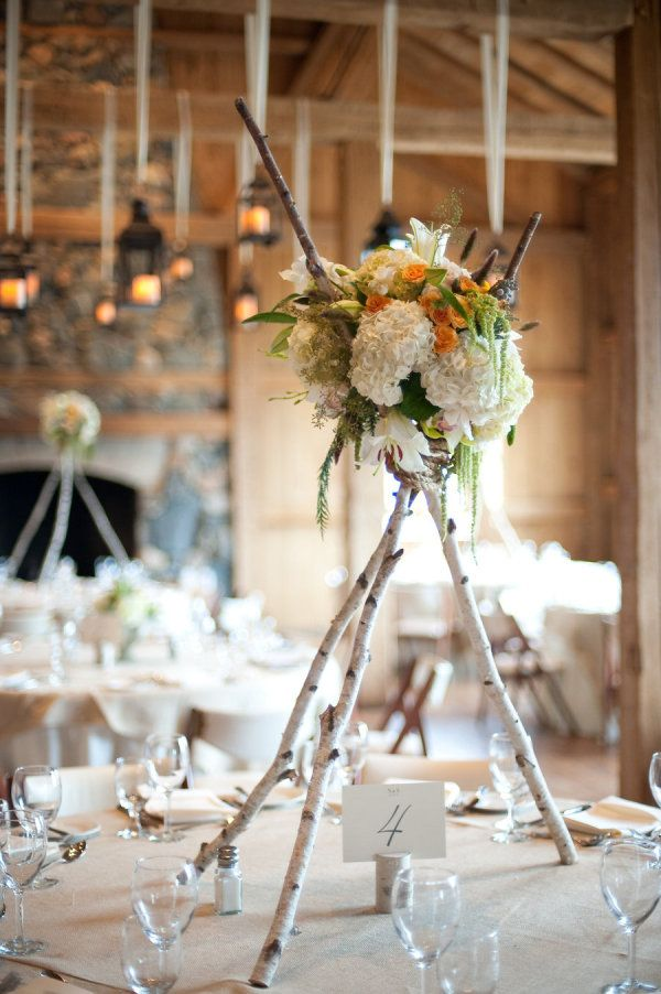tall birch log centerpieces with white, green and yellow flowers | rustic wedding reception | photo: paigeelizabeth.net