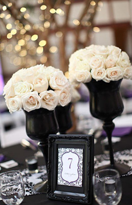 Love this idea. Black wine glasses as small floral arrangement around the main centrepiece.