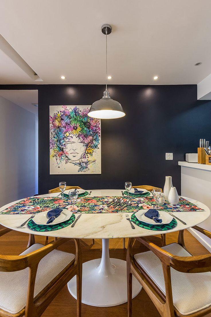 Decoração de apartamento sofisticado, moderno e jovial. Na sala de jantar mesa branca, cadeiras de madeira e obra de arte.