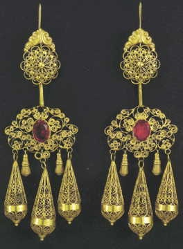 Gold filigree earrings with red stones from Corfu, 19th century. On the reverse is a ship, the emblem of Corfu. The pendent 'teardrops' are a characteristic feature of the Ionian Islands. Italian influences had been assimilated by the Epirote goldsmiths who came to the Ionian islands during the 1821 War of Independence. Athens, Benaki Museum,