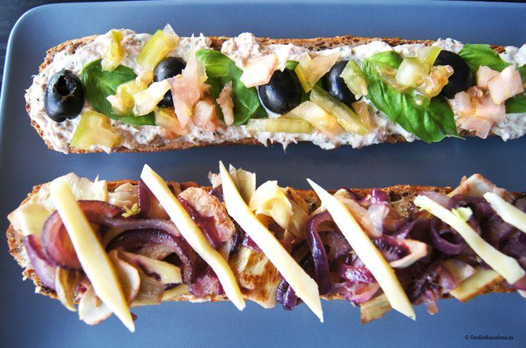 Sandwich de atún con corazón de alcachofa, aceitunas negras, albahaca, cebolla roja, tomate verde y queso gouda. El pan es integral con cere...