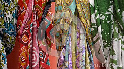 Colorful multicolored, patterned scarves hanging in row.