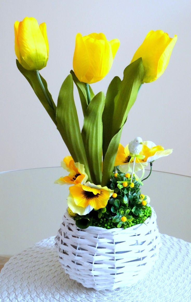 www.abgHomeArt.pl Ręcznie wykonany z dbałością o każdy szczegół wielkanocny stroik w białej wiklinowej osłonce z kwitnącymi tulipanami i kwiatuszkami w żółtej kolorystyce. Udekorowany ceramicznym ptaszkiem na piku oraz żółtymi nakrapianymi jajeczkami.  Efektowna i radosna wielkanocna dekoracja, która pięknie przyozdobi stół, komodę, czy też kominek, a także wprowadzi powiew wiosny. Idealny do każdego wnętrza.