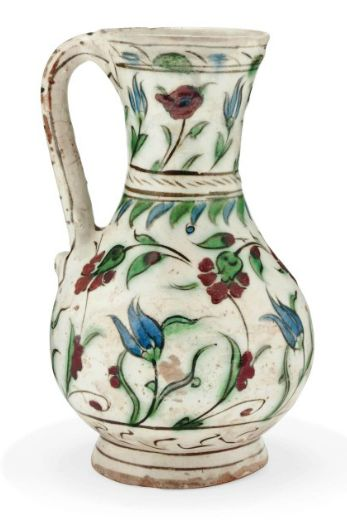 AN IZNIK POTTERY JUG   OTTOMAN TURKEY, EARLY 17TH CENTURY   Of rounded form on short flared foot with flaring neck, curved handle, the decoration on white ground with tulips and red flowers