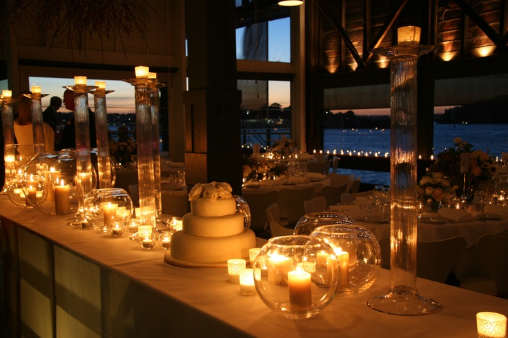 Create a sea of eco candle light by putting various sizes of beeswax candles into different sized fishbowls and candle holders. The glass reflects more light from every candle... and takes up more space - so it looks like you have hundreds of candles but can achieve the look with far fewer. In the background are Queen B tealights in small fishbowls and each table had 8 tealights in fishbowls. Flowers: Grandiflora Venue: Sydney Theatre Company