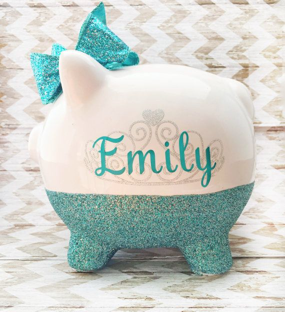 A precious personalized piggy bank will make the perfect gift for a new baby girl! Your new baby, granddaughter, niece, or godchild will treasure this keepsake piggy bank for years to come!  Each piggy bank is hand glittered and sealed to prevent glitter shedding, and embellished with a sparkling hair bow with a gem in the center.  The ceramic piggy bank is the carefully decorated with outdoor grade vinyl to ensure a lasting design. The vinyl design includes a sparkling silver tiara and the…