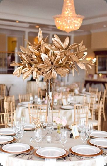 At the top of the stairs, the demilune table will have varied heights of cylinder vases with gold magnolia leaves, pillar candles in vases, skinny cylinder vases with gold swirls, and silver mercury glass votives.