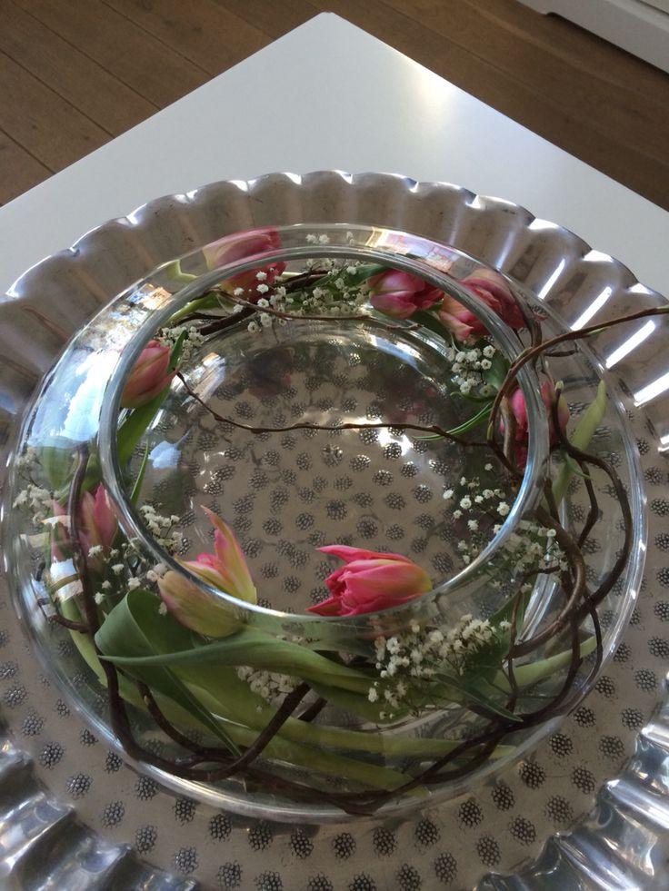 Tulpen en gipskruid met siertakken in ronde vaas op dienblad