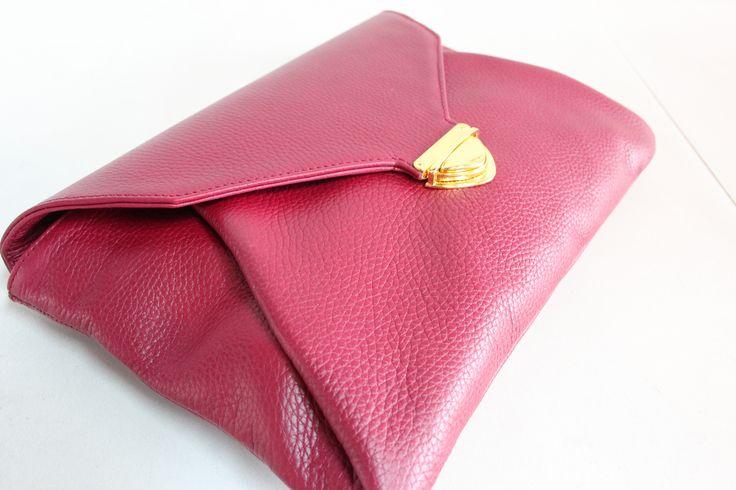 Sobre de piel color burgundy con broche rectangular dorado.