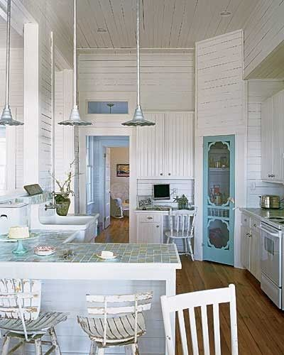 white kitchen with blue screen door on pantry