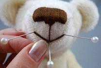 Фото 19. Теперь делаем примерку рта. Для этого втыкаем булавки в предполагаемые точки вышивки рта и, наматывая на булавки нить, смотрим, подходят ли очертания рта для нашего мишки. Следите за тем, чтобы булавки были воткнуты симметрично.
