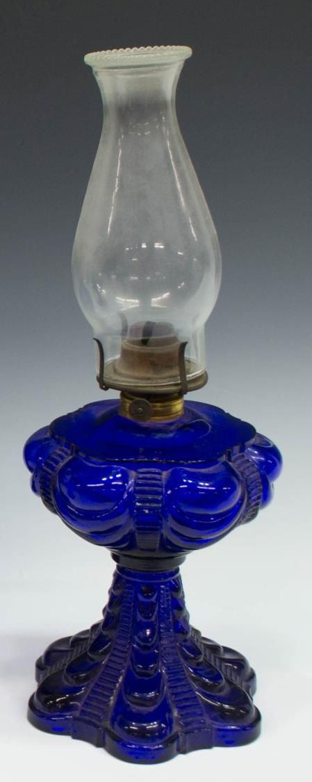 """(lot of 3) Victorian style cobalt drapery kerosene lamps, late 20th c., each with clear glass hurricane over brass Plume and Atwood burner, molded glass bases, dated 1976 underfoot, two matching, 19""""h, 12.75lbs **Provenance: From the historic Nelson-Crier house Round Rock, Texas** Start Price: $50.00"""