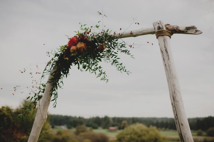 Simple drift wood arbor with dahlia, foliage and wild rose hips designed by Melissa at Flying Bear Farm + Design (Arbor constructed by dad-of-the-bride Alan, and now for rent through Flying Bear!) - Photography by carlybish.com   http://carlybish.com