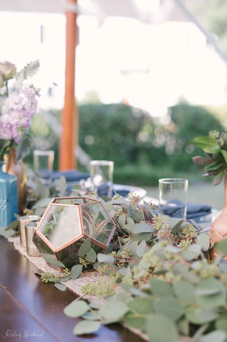 reception farm table is dressed with garland of seeded eucalyptus and copper terrariums filled