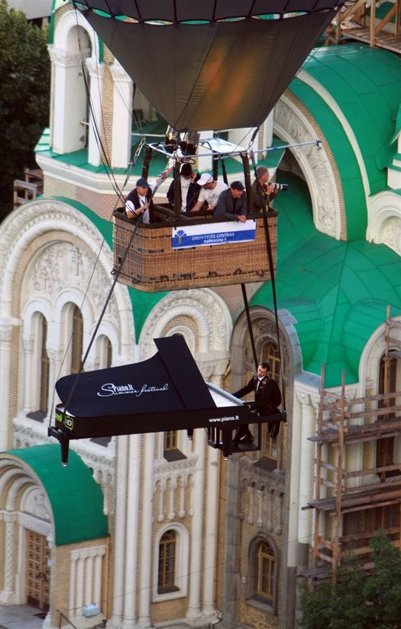A stuntman pretends to play the piano in the air as he and his cardboard instrument are lifted by a hot air balloon over Vilnius on August 10.