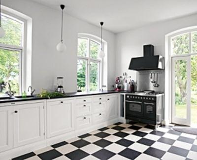 Rutigt golv i kök, vita luckor och svarta beslag.