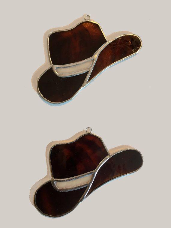 YEE-HAW ! Ce vitrail fait à la main chapeau de cowboy suncatcher est le cadeau parfait pour le cow-boy ou cow-girl dans votre vie!!  Ce chapeau de cowboy est fait de verre texturé brun et beige, avec une bande de verre de couleur crème.  Ce chapeau sapparie parfaitement avec la botte de cowboy suncatcher répertorié dans notre boutique (vendu séparément).  Environ 6 W x 3,75 H  (La liste est pour un chapeau de cow-boy).  (Ventouse incluse avec tout achat de suncatcher.)  NOTE au sujet de la…