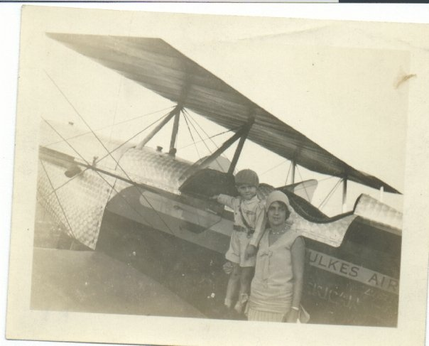 My dad with his mom, standing on his dad's plane (circa 1928)
