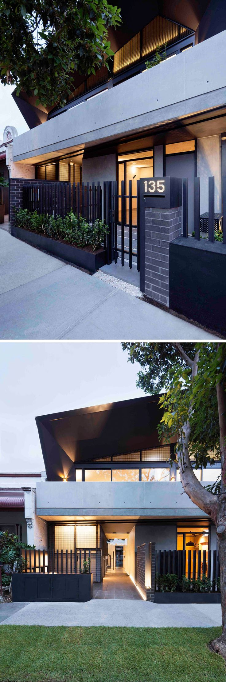 This modern apartment building has a black fence positioned behind planters that add a touch of greenery to the brick and concrete facade.