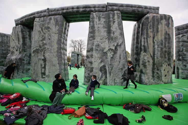 """Pagan moonbounce  Children play on April 20 at the base of  """"Sacrilege,"""" an interactive, full-scale inflatable replica of Stonehenge created by Turner Prize-winning Jeremy Deller for the Glasgow International Festival of Visual Arts in Scotland. The festival, which is put on for two weeks every two years, is showcasing more than 130 contemporary artists in permanent and temporary exhibition venues across the city."""