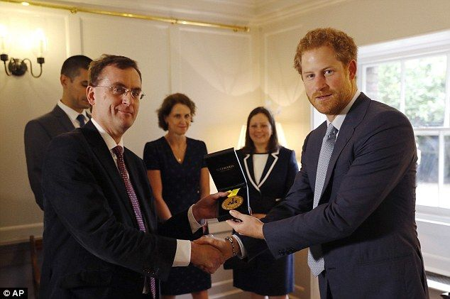 Prince Harry hands Sgt Elizabeth Marks' Invictus gold medal to consultant intensivist Dr Alain Vuylsteke, one of the medical staff who treated her when she fell gravely ill in 2014