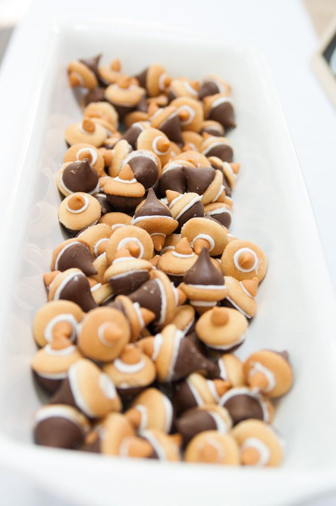 Acorn Dessert for Woodland themed birthday party. Hershey kiss Vanilla icing Vanilla wafer Butterscotch chip on top Attach the Hershey kiss to the wafer with the vanilla icing and then the butterscotch chip to chip to the wafer with vanilla icing.