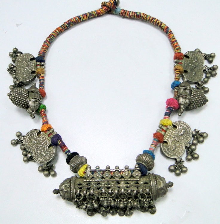 India   An old silver amulet pendant is strung on colourful yarn with six silver pendants   Silver alloy, exact silver content unknown.   Vintage piece.