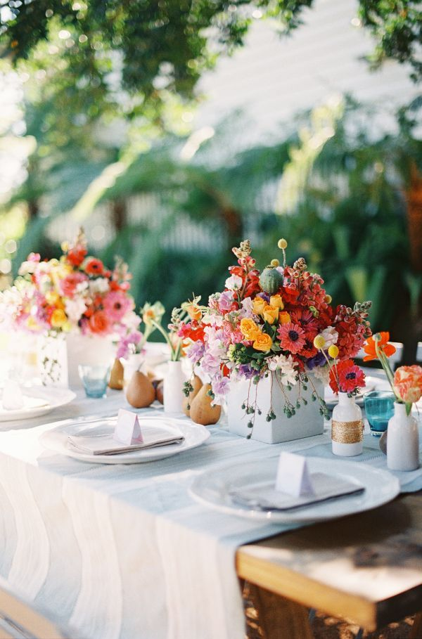 Colorful wedding inspiration, white linens, orange pink and yellow florals, fruit details, white escort cards, outdoor wedding inspiration