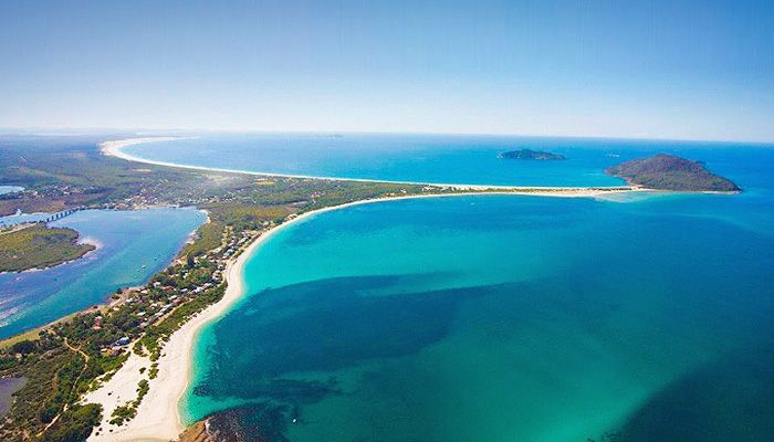 Aerial shot of Hawks Nest, NSW - the bay of  Port Stephens is in the right foreground, with Jimmy's Beach, at Hawks Nest, and Yacaaba headland; the Tasman Sea and Broughton Island beyond. The Myall River, leading northwards to Myall Lakes, is on the left.