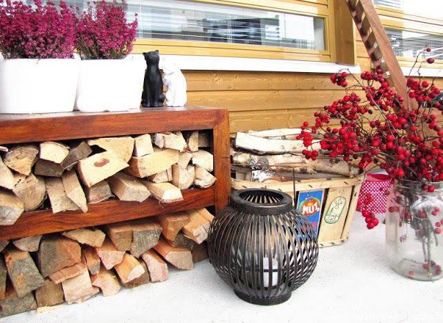 Balcony in the winter: heathers, hawthorn branches and firewood