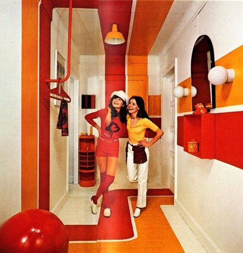 1970s orange and red interior and fashions. Because where to hang things is just so dingy-dang spiffy.