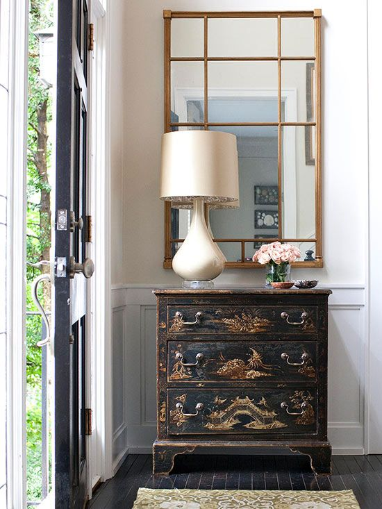 Asian Influence: This vignette packs a lot of punch in just a sliver of space, as pieces with Oriental flavor gather just inside the front door. The chest of drawers provides surreptitious storage as well as a landing spot for mail, keys, or a cup of coffee. The mirror offers a person one last look before heading out the door.